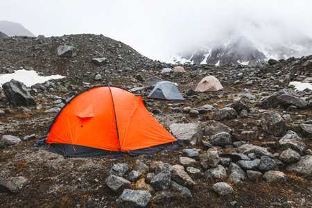 Ð¡amping with tents high in the mountains in winter. Fog, snow and cold weather. Mountain range and rocks on background 스톡 콘텐츠
