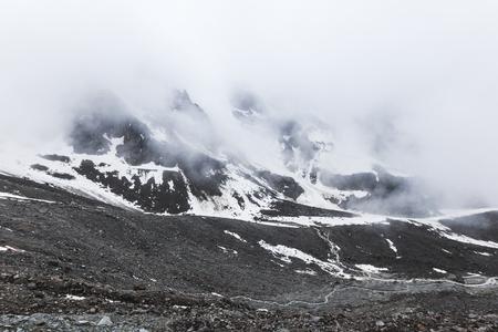Paisagem de montanha com pedras e névoa rastejante. Picos de neve altos nas nuvens, tempo frio. Grandes pedras em primeiro plano