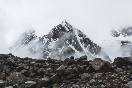 Mountain landscape with rocks and creeping fog. High snow peaks in the clouds, cold weather. Huge stones on foreground 스톡 콘텐츠