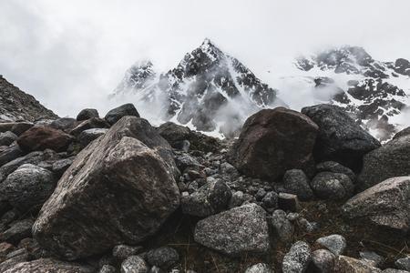 Górski krajobraz ze skał i pnący mgła. Wysokie szczyty śniegu w chmurach, zimna pogoda. Ogromne kamienie na pierwszym planie Zdjęcie Seryjne