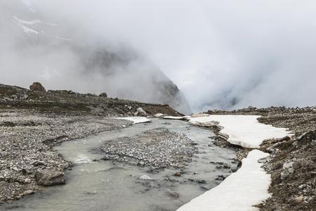 Górski krajobraz ze skał i pnący mgła. Wysokie szczyty śniegu w chmurach, zimna pogoda. Przepływ rzeki na pierwszym planie