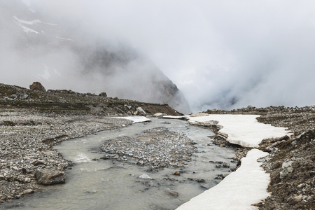 Mountain landscape with rocks and creeping fog. High snow peaks in the clouds, cold weather. River flow on foreground