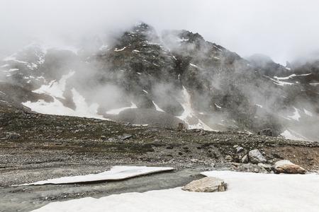 Paesaggio montuoso con rocce e nebbia strisciante. Alte cime di neve nelle nuvole, tempo freddo. Flusso di fiume in primo piano Archivio Fotografico