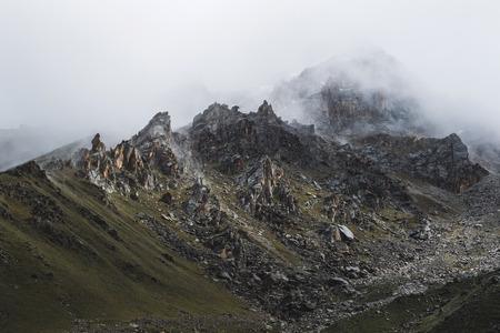 Paisagem de montanha com pedras e névoa rastejante. Picos altos nas nuvens, tempo frio. Turismo nas montanhas