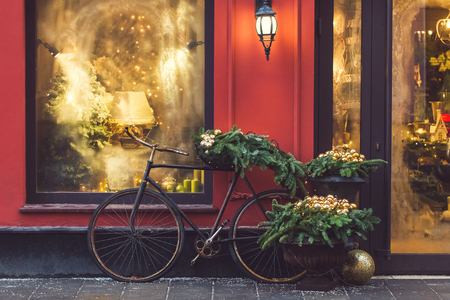 Christmas decorated showcase with old bicycle, fir branches, glass shiny toys and vintage lantern. Red building facade Zdjęcie Seryjne