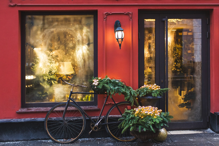 Christmas decorated showcase with old bicycle, fir branches, glass shiny toys and vintage lantern. Red building facade 스톡 콘텐츠