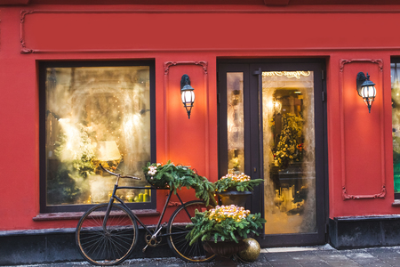 Christmas decorated showcase with old bicycle, fir branches, glass shiny toys and vintage lantern. Red building facade Archivio Fotografico