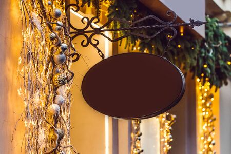 Oval metal black forged shop sign in christmas lights and decorations. Empty space for text, logo, sign. New year atmosphere 스톡 콘텐츠