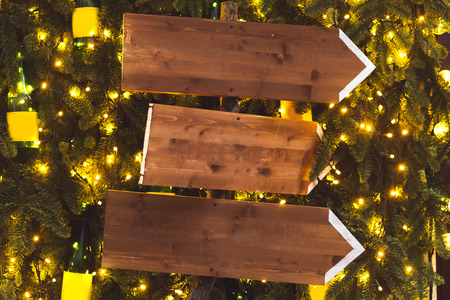 Three wooden pointer on background with fir branches in garlands. Christmas lights decoration, new year party Archivio Fotografico