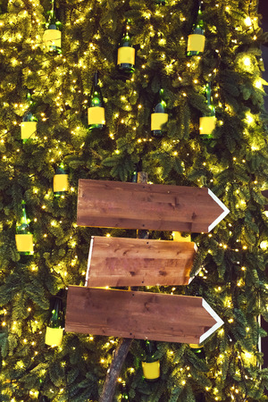 Three wooden pointer on background with fir branches in garlands. Christmas lights decoration, new year party 스톡 콘텐츠
