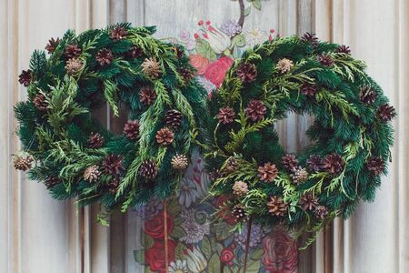 Facade decoration with christmas wreaths with fir branches and cones. Greeting arrangement on entrance with beautiful New Year toys Stock Photo