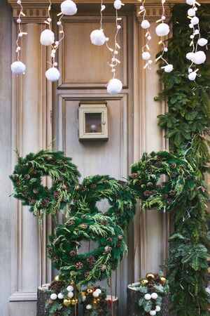 Facade decoration with christmas wreaths with fir branches and cones. Greeting arrangement on entrance with beautiful New Year toys 스톡 콘텐츠