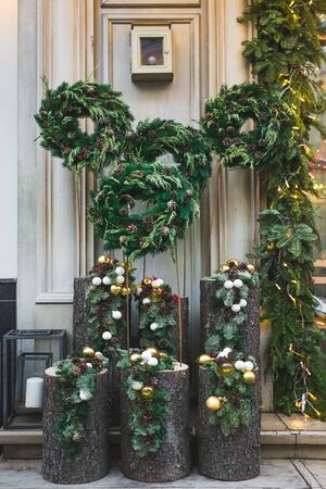 Facade decoration with christmas wreaths with fir branches and cones. Greeting arrangement on entrance with beautiful New Year toys Archivio Fotografico