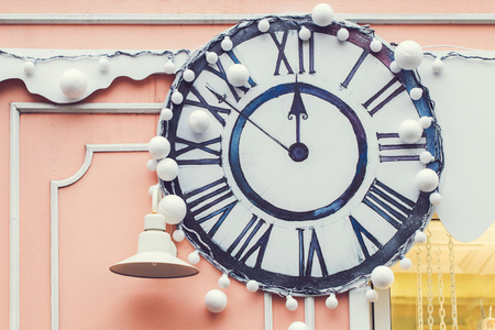 Handmade wall clock decorated with white balls for Christmas, outside on building facade at street