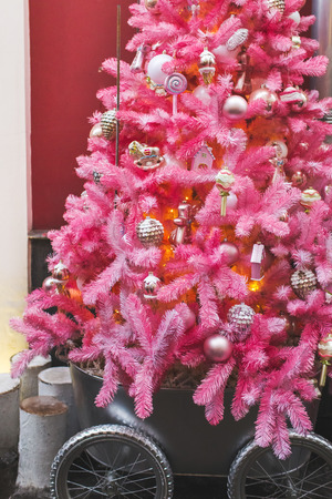 Unusual artificial Christmas tree decoration on pink fir branches, cute glass handmade toys. New Year Decor