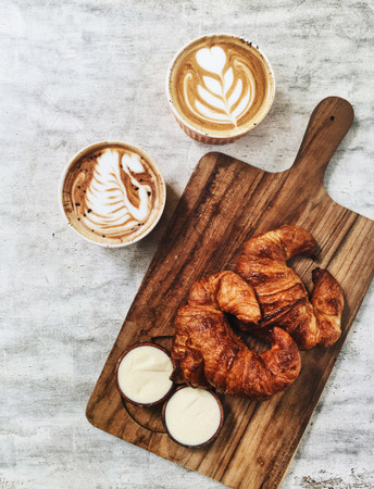 Two fresh crispy butter croissant on wooden plate and two hot aroma cappuccino. French breakfast, textured background Stock Photo