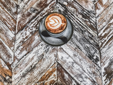Cup of coffee with beautiful tableware on wooden shabby rustic textured background. Empty place for sign, text