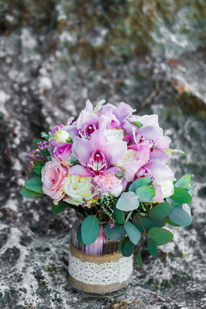 Tender bridal bouquet with pink orchids and white roses in glass pot. Wedding arrangement and decorations
