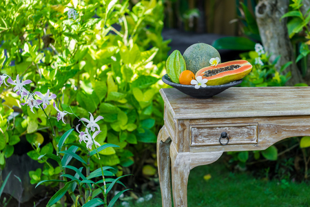 Fruit plate with fresh Bali fruits papaya, orange, melon and star fruit on wooden vintage table in tropical garden. Frangipani flowers