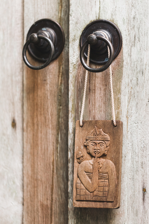 Wooden plate in balinese stile hanging on metal door knob. Textured background. Old rustic style. Dont disturb sign symbol Stock Photo