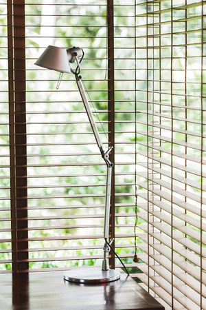 Metal high desk lamp in office, blinds on windows, minimalist style Stock Photo