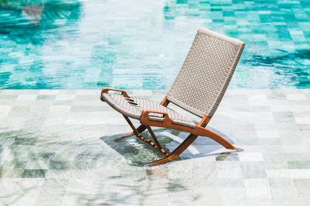 Folding rattan chair chaise longue by the pool. Clear transparent water