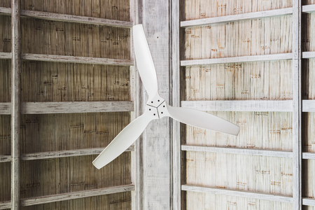 White ceiling fan under wooden roof, tropical house interior