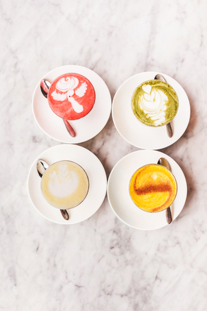 Four different colored latte coffee, style of foam art, natural organic beverages in modern cafe on white marble background