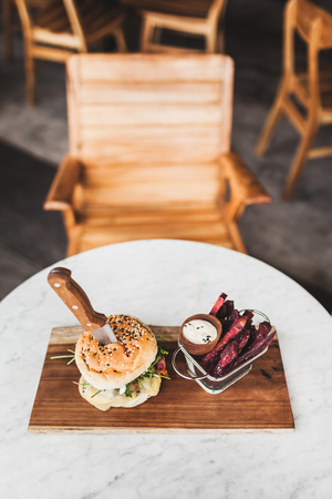 Fresh tasty burger with knife inside with sauce and fried purple sweet potato on side. On white round table on wooden board