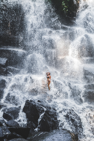 Woman enjoying under stream of big and beautiful cascade waterfall. Girl with slim body and long hair. Kanto Lampo in Ubud area