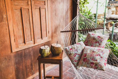 Hammock with colorful pillows and wooden table with two fresh coconuts. Wooden house 写真素材