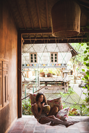 Woman sitting in hammock with colorful pillows and drinking fresh young coconut. Wooden village house in rustic style 写真素材