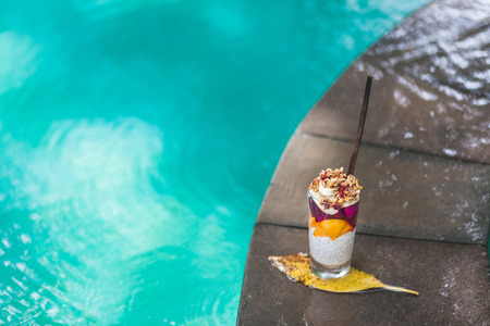 Coconut chia pudding coctail with fresh mango, banana and dragonfruit on edge of pool with clean turquoise water. Tropical style