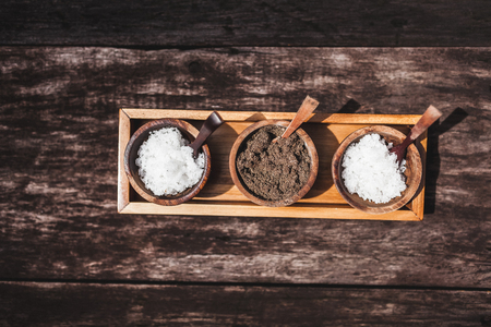 Salt, shugar and pepper set in small wooden saucer on dark wooden background. View from above