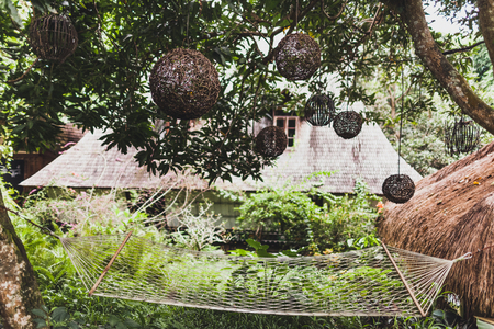 Hammock in green garden with wicker handmade lamps, tropical Bali style. Rustic style