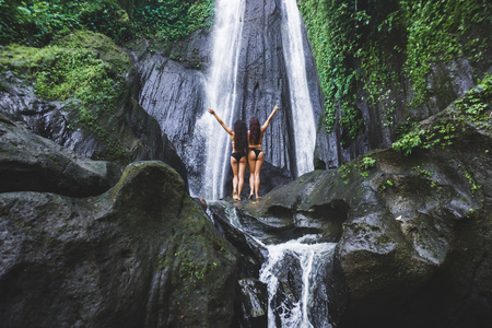 Two slim women relaxing near beautiful waterfall in Bali jungle. Nature adventure Dusun Kuning in Ubud area 写真素材