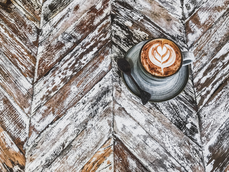 Cup of coffee with beautiful tableware on wooden shabby rustic textured background. Empty place for sign, text, logo.