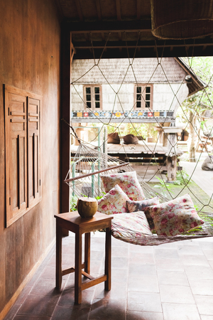 Hammock with colorful pillows and wooden table with fresh young coconut. Wooden house hippie style