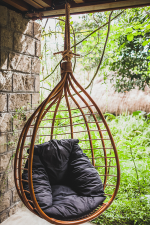 Rattan hanging wicker chair with black pillow in garden, summertime