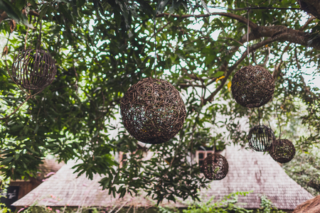Decorative round wicker lanterns hanging in garden, modern style