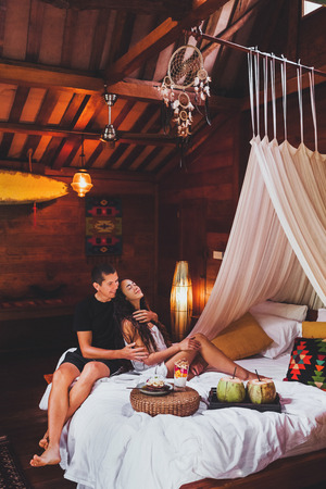 Young couple in love having breakfast in bed in traditional indian wooden house in hippie style 写真素材