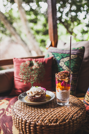 Breakfast outside on sofa with colorful pillows with traditional east ornaments. Pancakes with banana, coconut and chia pudding with fresh fruits 스톡 콘텐츠