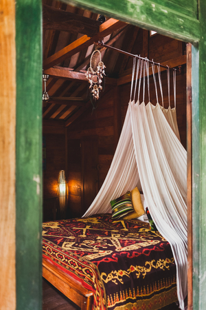 Hippie style wooden room with traditional bed covered by colorful blanket with ornament. Hanging baldachin and dreamcatcher 写真素材