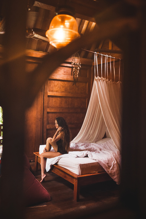 Woman in black lingerie sitting on bed in ethnic wooden house in morning