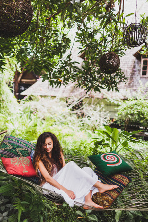 Woman in white dress relaxing in hanging hammock in bali garden. Round wooden wicker lantern hanging on tree
