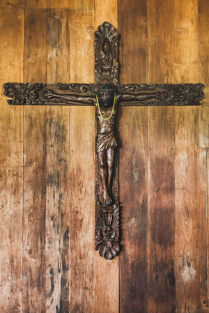Carved figure of Jesus hanging on wooden background wall