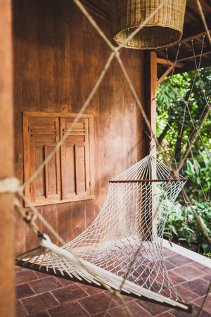 Hammock hanging in hipster wooden house. Place for relax, tropical mood
