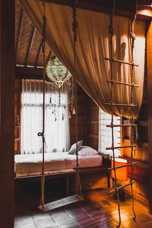Child playing room in rustic village style inside wooden house with swing, bed and hanging ladder 写真素材