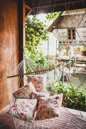Hammock with colorful pillows hanging in hipster wooden house. Place for relax, tropical mood 写真素材