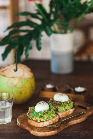Healthy organic tasty breakfast - avocado on toast with poached eggs, fresh young coconut